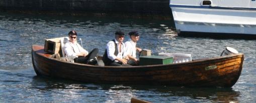 Båtfolk med strileklede, kasjetthua er på plass