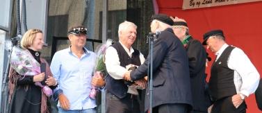 Gerhard Eikeland ble gratulert av styreleder i Torgdagen. Vidar Tveranger hjelp styret i Torgdagen med å kåre Best restautrerte båt